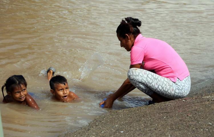 Niños hondureños víctimas de Eta e Iota se bañan en pestilentes aguas estancadas